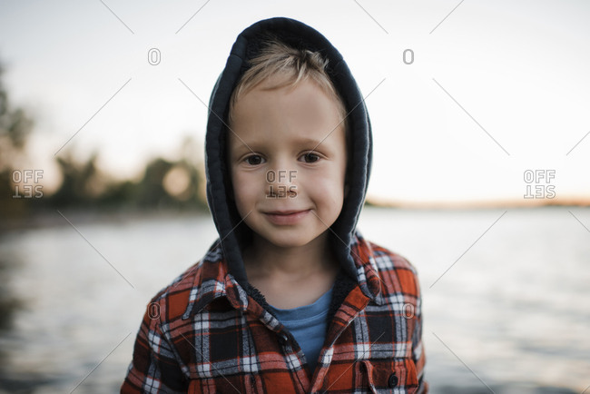 Portrait of cute boy in hooded shirt standing by lake against clear sky during sunset