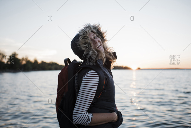 Portrait of happy woman with backpack standing at lakeshore against clear sky during sunset