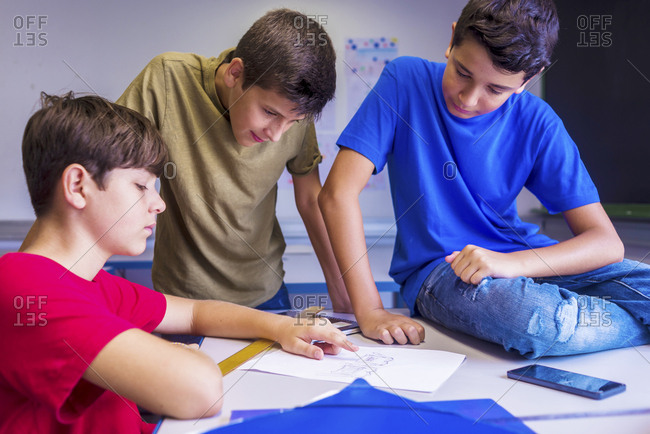 Schoolboys discussing paper in classroom