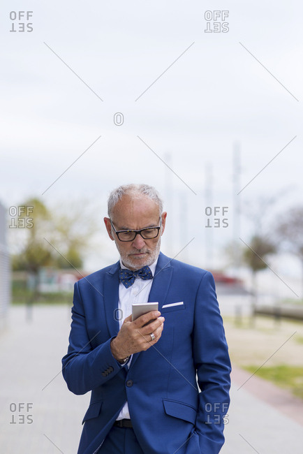 Confident senior man in suit using smart phone while standing on footpath against sky