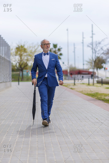 Confident senior man in suit with umbrella walking on footpath against sky
