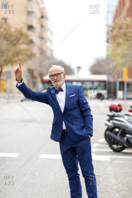 Confident senior man in suit hailing while standing on city street