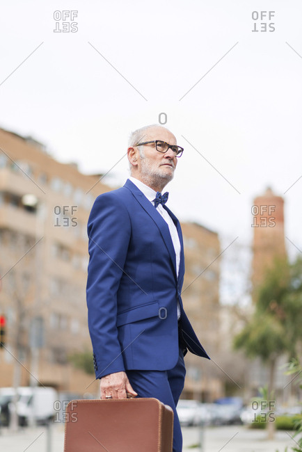 Side view of senior man in suit carrying suitcase while walking on city street against clear sky