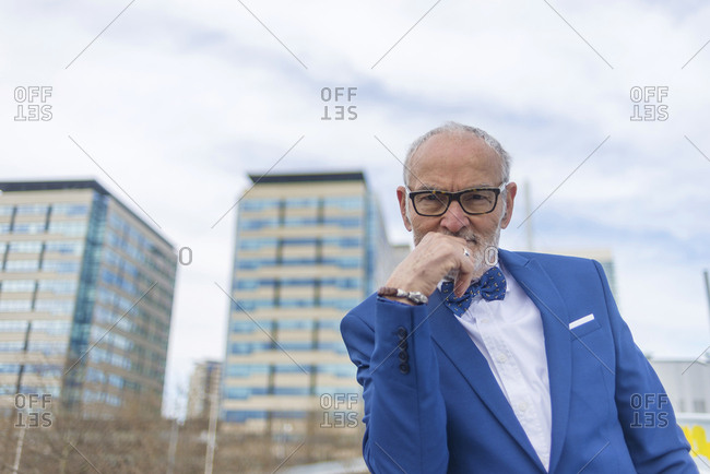 Low angle portrait of confident senior man in suit standing against cloudy sky