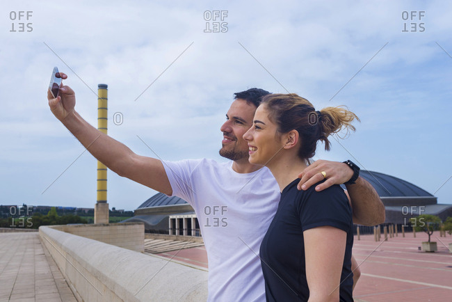 Couple taking selfie with mobile phone while standing against cloudy sky at park