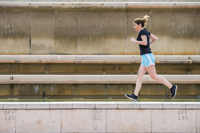 Side view of woman running on retaining wall against wall at park