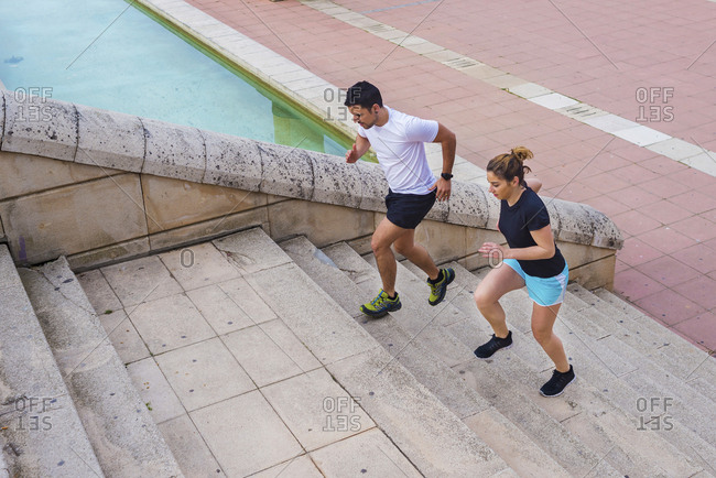 High angle view of couple running on steps at park in city