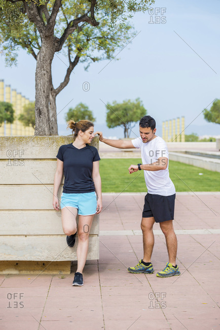 Man checking time while talking to woman leaning on wall at park