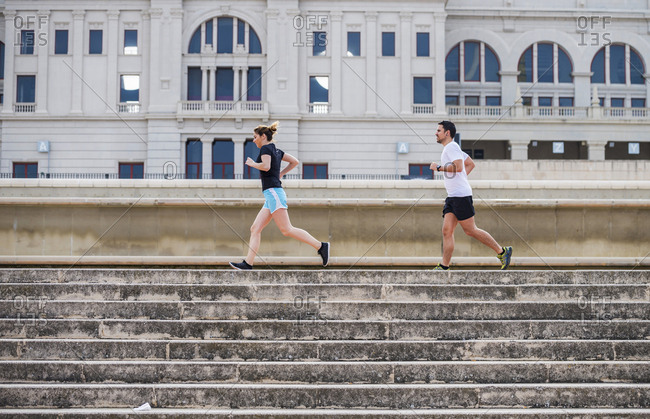 Side view of couple running on steps against building in city
