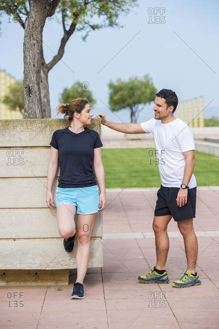 Couple talking while standing against sky at park