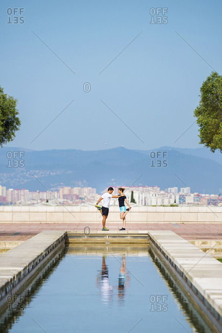 Side view of couple exercising while standing on retaining wall against clear blue sky at park