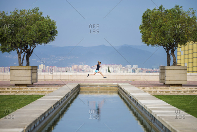Side view of woman running on retaining wall against clear blue sky at park