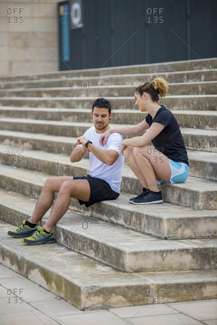 Couple talking while sitting on steps at park