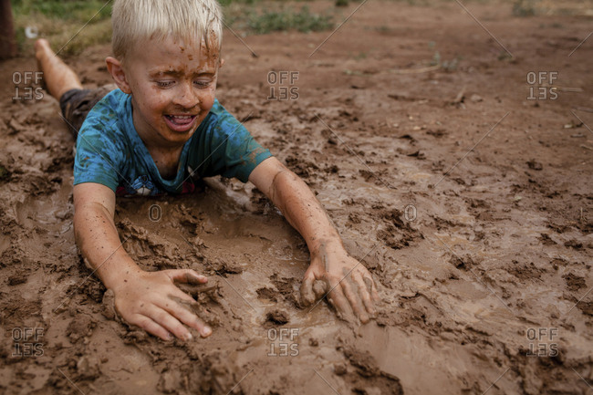 High angle view of playful boy lying on muddy field in yard