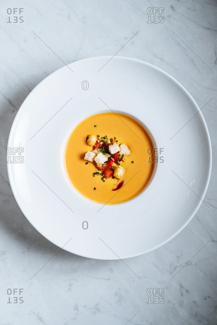 Bowl of creamy pumpkin soup topped with croutons and green onions