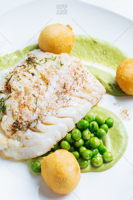 Fillet of white fish served with green peas and hushpuppies