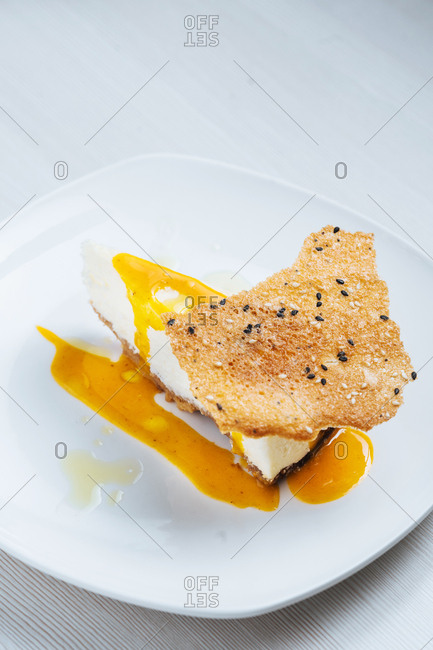 Piece of cheesecake topped with sauce and served with brittle