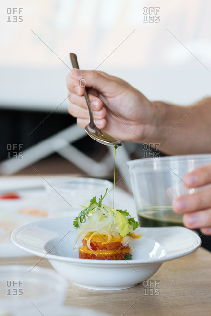 Person drizzling olive oil over gourmet salad