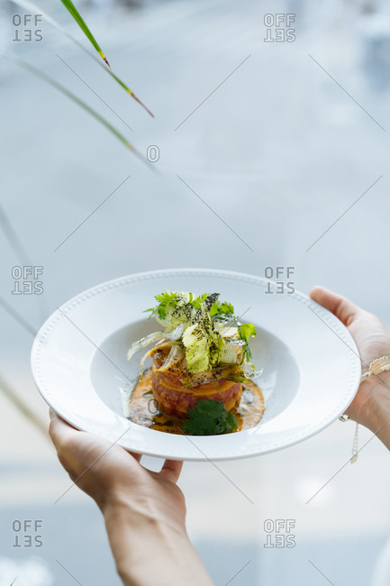 Person holding a gourmet salad with tomatoes