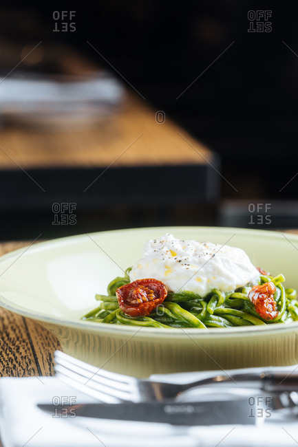 Dish with green noodles and sun-dried tomatoes topped with a poached egg