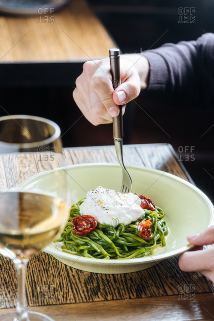 Person eating a dish of spinach linguine