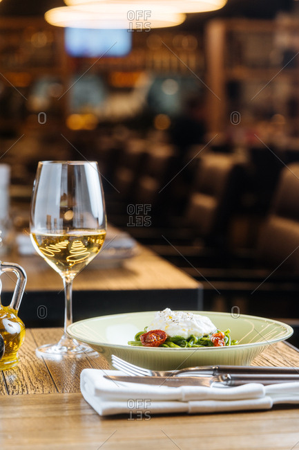Spinach linguine served with a glass of white wine