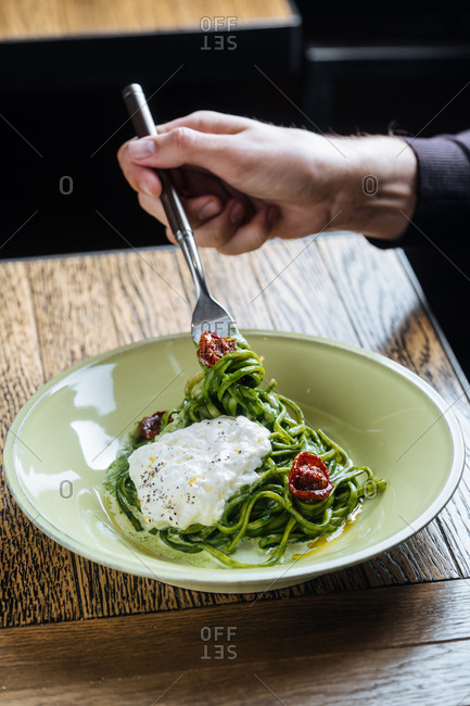Person using a fork to twirl spinach linguine noodles