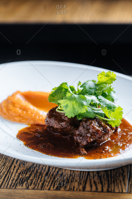 Dish with cooked beef served with sauce and topped with fresh cilantro