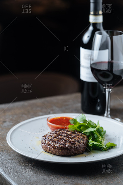 Grilled beef patty served with a glass of red wine and bottle