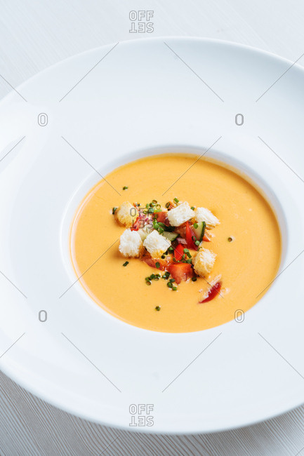 Bowl of creamy pumpkin soup topped with croutons, tomatoes, and green onions