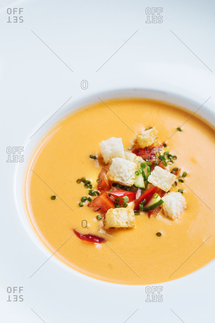 Close up of bowl of creamy pumpkin soup topped with croutons, tomatoes, and green onions