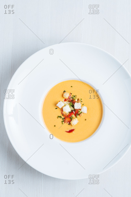 Bowl of creamy squash soup topped with bread and green onions