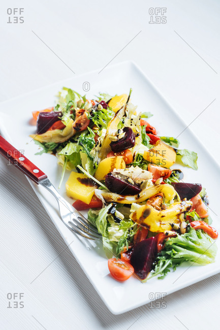 Fresh salad with fruit drizzled with balsamic vinegar
