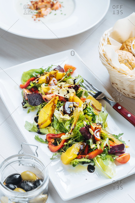 Fresh salad served with soup, bread, and olives