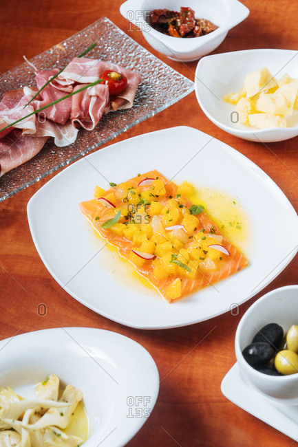 Salmon and prosciutto served on table with olives, cheese, and sun-dried tomatoes
