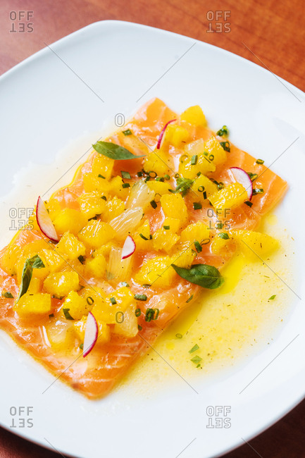 Fillet of salmon topped with fresh pineapple, basil, green onions, and radishes