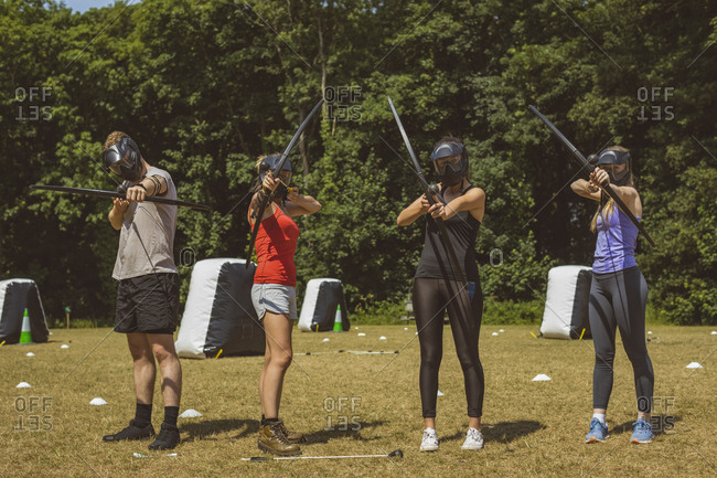 Group of people training archery at boot camp on a sunny day