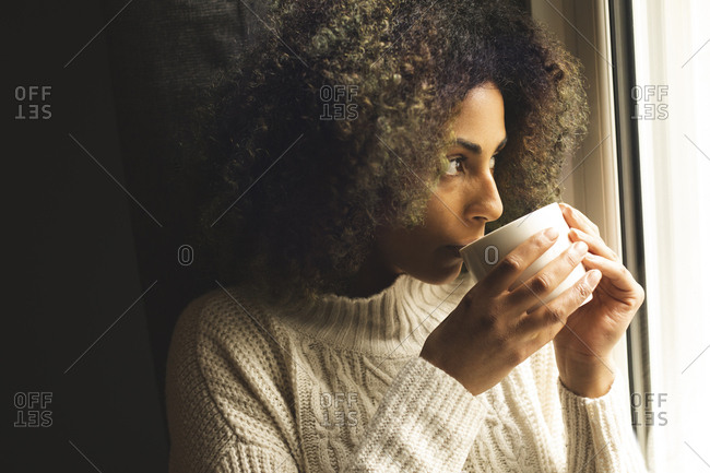 Young woman having coffee at home