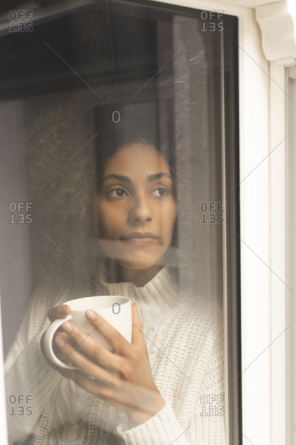 Thoughtful woman having coffee at home