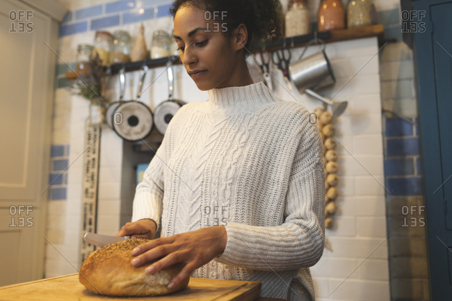 Woman cutting loaf of bread in kitchen at home