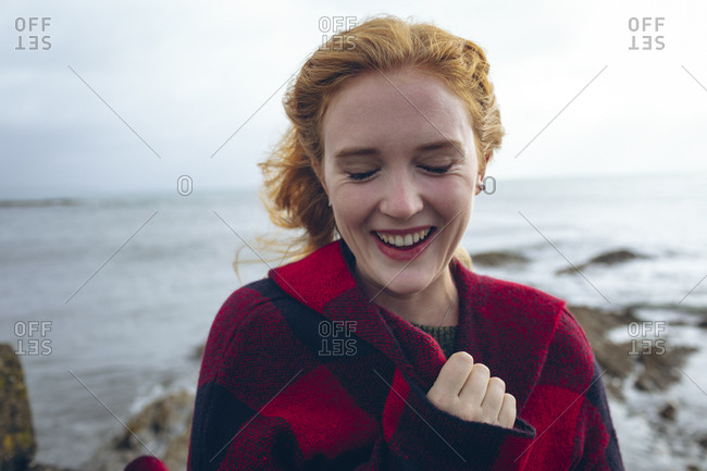 Redhead woman smiling in the beach