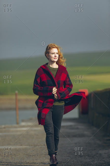 Thoughtful redhead woman walking in the beach