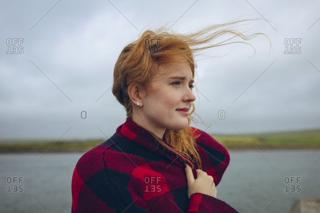 Thoughtful redhead woman standing in the beach