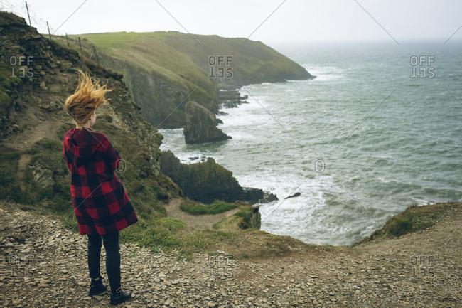Rear view of redhead woman standing near beach