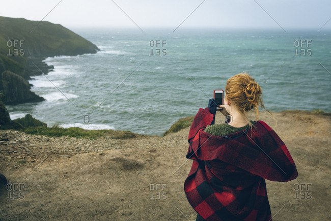 Rear view of woman clicking photos with mobile phone in the beach