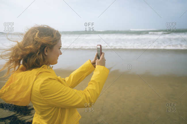 Redhead woman clicking photos with mobile phone in the beach