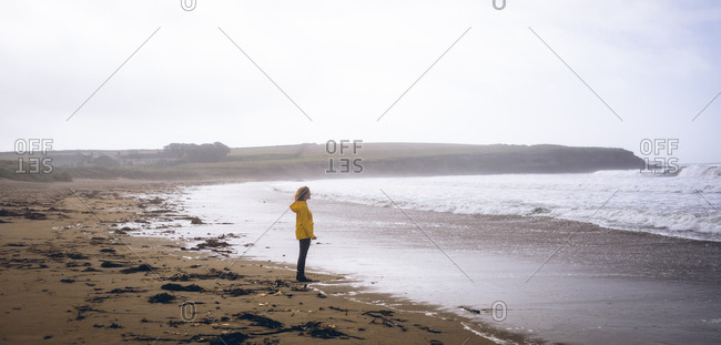 Side view of woman standing in the beach