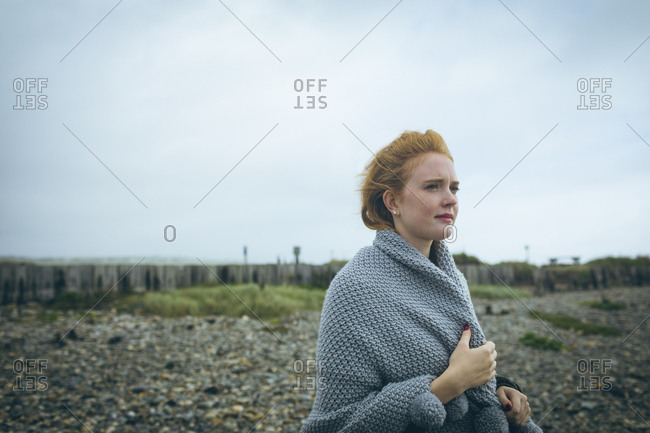 Thoughtful woman in grey jacket standing near beach