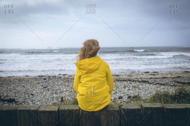Woman sitting on the fence in the beach