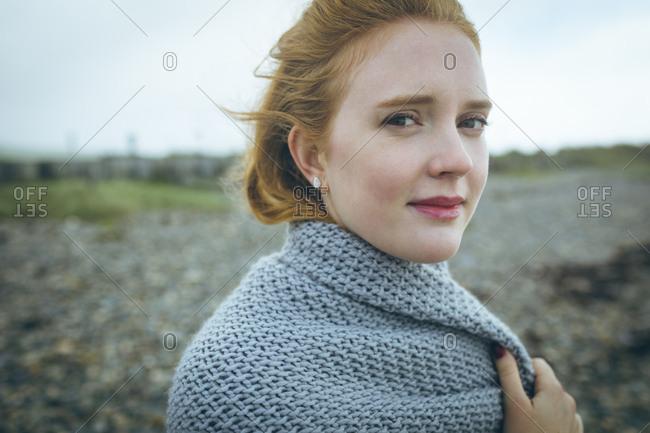 Portrait of woman in grey jacket standing near beach